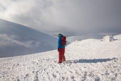 Abenteurer, mit Snowboard steht auf der Bergspitze Stockbilder
