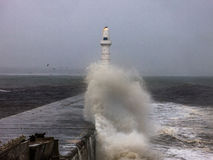 Aberdeen Lighthouse struck by waves on water break. Aberdeen lighthouse is struck by waves during a storm smashing against the break water Stock Photography