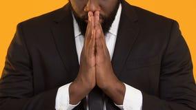 Abergläubischer schwarzer Mann, der vor dem wichtigen Abkommen, hoffend für Erfolg betet stock footage