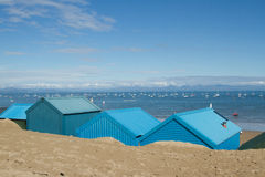 Abersoch beach huts. Blue beach huts in the sand look out over the sea with yachts and mountains in the distance at Abersoch, Gwynedd, Wales, UK Stock Photos