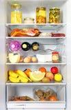 Aberto do refrigerador armazenado completamente carregado acima com o alimento e o ingredie fresco Imagens de Stock