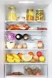 Aberto do refrigerador armazenado completamente carregado acima com o alimento e o ingredie fresco Fotografia de Stock Royalty Free