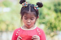 Abertura asiática linda de la muchacha del niño y dinero de la mirada en sobre rojo Imagen de archivo libre de regalías