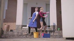 A abertura da porta e a dança positiva da jovem mulher e do homem no patamar da casa Casa de limpeza dos pares junto video estoque