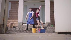 A abertura da porta e a dança positiva da jovem mulher e do homem no patamar da casa Casa de limpeza dos pares junto filme