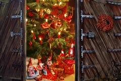 Abertura de la puerta en un cuarto con el árbol de navidad y el regalo Imagenes de archivo