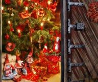 Abertura de la puerta en un cuarto con el árbol de navidad y el regalo Foto de archivo libre de regalías