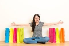 A abertura feliz da mulher arma o gesto que mostra sacos foto de stock