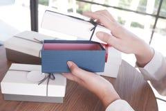 Abertura femenina una caja de regalo para el regalo, actual concepto fotos de archivo