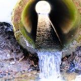 Abertura redonda da tubulação de esgoto Fluxo da drenagem da água do derretimento fotos de stock royalty free