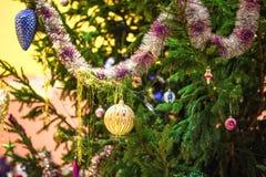abete rosso in tensione decorato con i giocattoli di Natale, le ghirlande e le palle all'aperto, nuovo anno immagini stock