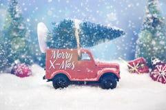 Abeti con il Buon Natale dei fiocchi di neve e della neve immagine stock