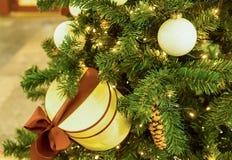 Abeto adornado con una guirnalda que brilla intensamente con bombillas, una bola brillante blanca de la Navidad y una caja poner  Foto de archivo