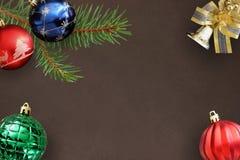 Abeto de la rama de la Navidad, azul, globos acanalados rojos y verdes ondulados, campana decorativa en oscuridad Fotos de archivo libres de regalías