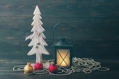 Abeto del Año Nuevo, lámpara de la Navidad y esferas decorativos de madera del vidrio en un fondo de madera Imagen de archivo libre de regalías