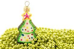 Abeto del juguete de la decoración de la Navidad en la gota de oro aislada Imagenes de archivo