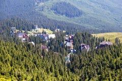 Abeto e casas verdes da vila Dragobrat contra o fundo das montanhas Carpathian no verão ucrânia Foto de Stock