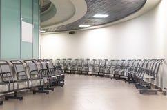 Abfahrtaufenthaltsraum in einem Flughafen mit Stühlen Rundes galary Stockbilder