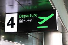 Abfahrtzeichen auf Englisch und Myanmar-Sprache mit Symbol der Fläche entfernen sich im Grün auf schwarzer Farbe am Tor Nr. 4 stockfotos