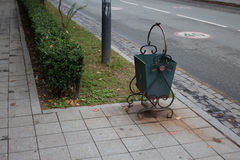 Abfall auf der Straße im Stadtöffentlichen platz, aus dem Mülleimer heraus Grüner Abfalleimer auf Straßenseite Stockfoto