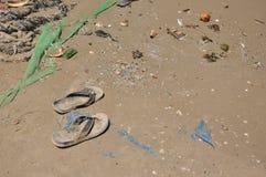 Abfall auf Sand und ein Paar Flipflops stockfotos