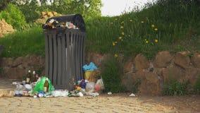 Abfall, der aus ?berf?lltem Abfalleimer heraus versch?ttet wird stock video footage