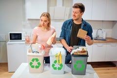 Abfall, der zu Hause sortiert Lächelnde junge Familie, die Plastik, Papier, anderer Abfall in den Abfallbiobehältern in der Küche stockbild