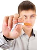 Abfall des jungen Mannes eine Zigarette Stockbild