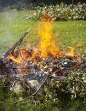 Abfall im Feuer, arbeiten illegaler Brandabfall im Garten Lizenzfreie Stockfotos