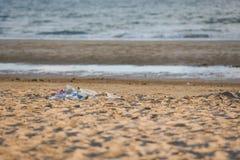Abfall im Meer mit Taschenplastikflasche und in anderem sandigem schmutzigem Meer des Abfallstrandes auf der Insel/dem Umweltprob lizenzfreie stockbilder