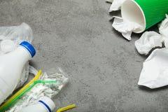 Abfall mit einer Plastikflasche, einem Plastik und einem Papier auf einem grauen Hintergrund, Draufsicht Leerer Platz f?r Text lizenzfreies stockbild