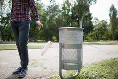 Abfall von Umwelt Ein leeres der Plastiktrinkflasche, die auf dem Straßenboden am grünen Park mit Unschärfe verunreinigt Stockfotos