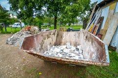 Abfallbehältermüllcontainer des Baus an Wohnhaus const stockfotografie