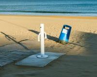 Abfalleimer auf dem Strand nah an der Dusche Stockfotografie