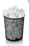 Abfalleimer, der mit dem zerknitterten Papier lokalisiert auf Weiß überläuft Stockfotografie