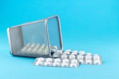 Abfalleimer mit Sätzen der weißen Kapseln und der Pillen verpackte in den Blasen mit Kopienraum auf blauem Hintergrund Fokus auf  Lizenzfreies Stockbild
