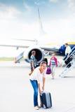 Abflug - junge Frau an einem Flughafen Stockfotografie