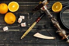 Abgebaute Teile der Huka auf einem hölzernen Hintergrund mit orange Franc Stockfoto