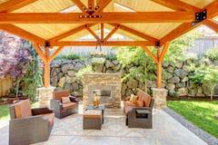 Abgedeckter Außenpatio mit Kamin und Möbeln. Stockbild