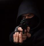 Abgedeckter Räuber mit der Gewehr, die in die Kamera zielt Stockfoto
