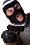 Abgedeckter Verbrecher zeigt eine Gewehr Stockfoto