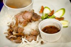 Abgefeuertes Schweinefleisch auf Reis mit Suppe und thailändischer Art-Soße stockbild