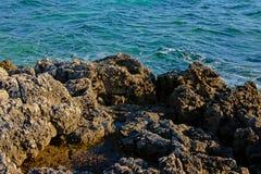 Abgefressene graue vulkanische Felsen auf der Küste des adriatischen Meeres Stockbilder