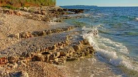 Abgefressene vulkanische Felsen und Kiesel auf der Küste des adriatischen Meeres Lizenzfreie Stockfotos