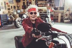 Abgehende Großmutter, die Motorrad im Mechanikershop fährt stockfotos