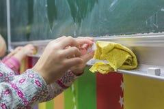 abgehobener Betrag des kleinen Mädchens auf der Tafel, Kreide stockfoto