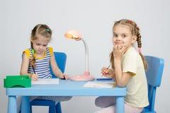 Abgehobener Betrag mit zwei Schwestern, der am Tisch sitzt Lizenzfreies Stockbild