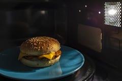 Abgekühlter, appetitanregender Cheeseburger mit einem Brötchen des indischen Sesams, Fleisch und Käse in einer blauen Platte wurd stockbild