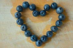 Abgelassene Herzform der schwarzen Oliven auf hölzerner Draufsicht Lizenzfreie Stockbilder