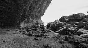 Abgelegene Bucht mit enormen Küstenfelsen, Schwarzweiss-Foto Lizenzfreie Stockbilder